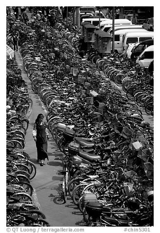 Woman walking in a bicycle parking lot. Chengdu, Sichuan, China (black and white)