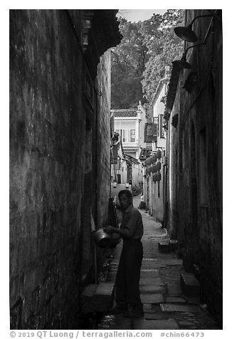 Man using stream water in alley. Hongcun Village, Anhui, China (black and white)