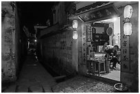 Shopkeeper and alley at night. Hongcun Village, Anhui, China ( black and white)