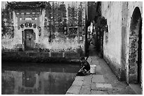 Woman washes laundry in Moon Pond. Hongcun Village, Anhui, China ( black and white)