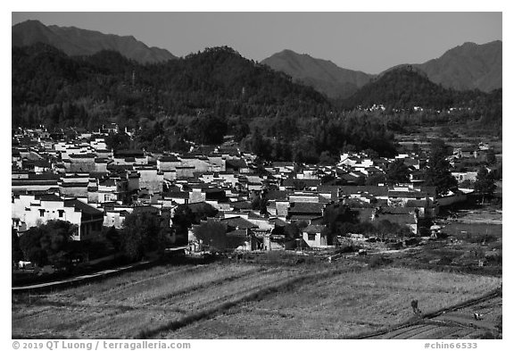 Field workers and village from above. Xidi Village, Anhui, China (black and white)