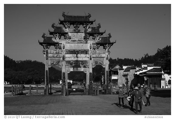 Villagers heading towrds fields, and Hu Wenguang Memorial Arch. Xidi Village, Anhui, China (black and white)