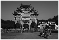Villagers heading towrds fields, and Hu Wenguang Memorial Arch. Xidi Village, Anhui, China ( black and white)