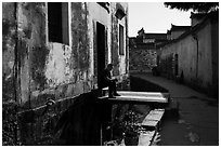 Man sitting in front of house on bridge over stream. Xidi Village, Anhui, China ( black and white)