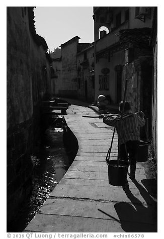 Woman carrying buckets. Xidi Village, Anhui, China (black and white)