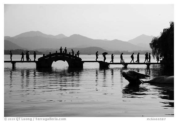 People walking on Yongjin Bridge, West Lake. Hangzhou, China (black and white)
