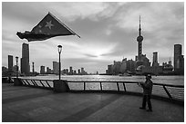 Man flying kite with Chinese flag attached on line, the Bund. Shanghai, China ( black and white)