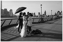 Bride and groom setting up for photos, the Bund. Shanghai, China ( black and white)
