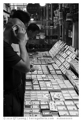 Man listening at insect. Shanghai, China (black and white)