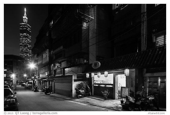 Black and white picture photo dark street store with lanters and taipei 101 taipei taiwan