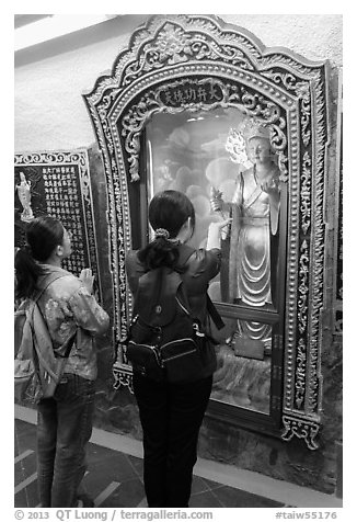 Women pray to deity, Guandu Temple. Taipei, Taiwan (black and white)