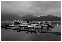 Pier with distant lights of Itashao Village and Syuanzang Temple at dawn. Sun Moon Lake, Taiwan ( black and white)
