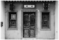 Facade of concrete building with wooden doors and windows. Lukang, Taiwan (black and white)