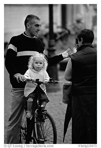 Blond little girl sitting on bicycle. Bruges, Belgium (black and white)