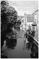 Boat on a canal lined with houses and trees. Bruges, Belgium (black and white)