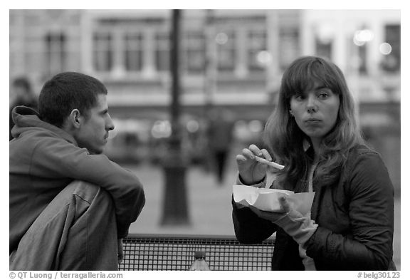 Young woman eating fries, Markt. Bruges, Belgium (black and white)