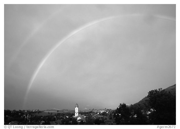 Rainbow over Nesselwang and St Andreas church. Bavaria, Germany (black and white)