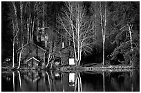 Wooden house reflected in a lake at sunset. Central Sweden (black and white)