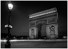 Street lamp and Etoile triumphal arch at night. Paris, France (black and white)