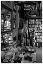 Picking-up a book in Shakespeare and Co bookstore. Quartier Latin, Paris, France ( black and white)