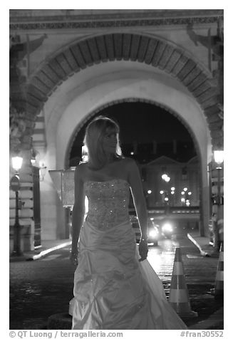 Woman in bridal gown in front of the Louvre by night. Paris, France (black and white)
