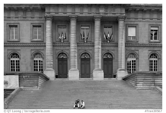 Two tourists sitting on the stairs of the Palais de Justice. Paris, France