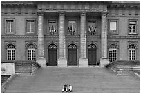 Two tourists sitting on the stairs of the Palais de Justice. Paris, France (black and white)