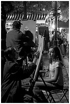 Artists drawing portraits at night on the Place du Tertre, Montmartre. Paris, France (black and white)
