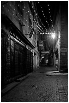 Lonely street by night with Tabac sign and Christmas lights. Carcassonne, France (black and white)