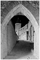 Ramparts and tower framed by gate at night. Carcassonne, France (black and white)