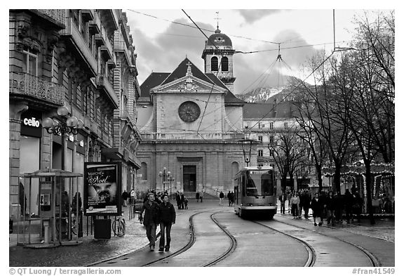 Street with people walking, tramway and church. Grenoble, France (black and white)