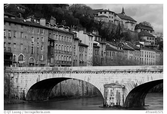 Stone bridge and brightly painted riverside townhouses. Grenoble, France (black and white)
