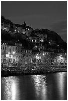 Hillside houses and Christmas lights reflected in Isere River. Grenoble, France (black and white)