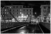 Pedestrians on suspension bridge at night. Grenoble, France ( black and white)