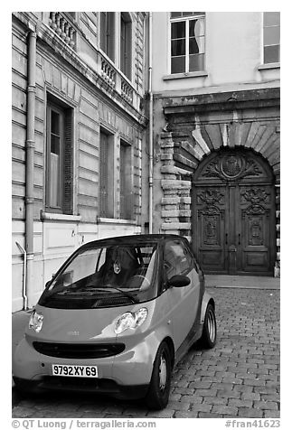 Tiny car on coblestone pavement in front of historic house. Lyon, France (black and white)