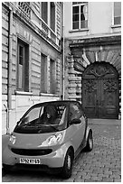 Tiny car on coblestone pavement in front of historic house. Lyon, France ( black and white)
