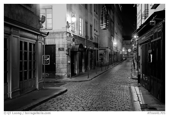 Narrow cobblestone street in historic district at night. Lyon, France (black and white)