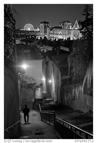 Man walking down stairs from Fourviere Hill, with St-Jean Cathedral below. Lyon, France (black and white)