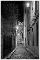 Narrow street leading to Palais des Papes at night. Avignon, Provence, France (black and white)