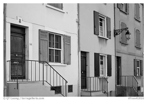 Facade of townhouses with colorful shutters. Arles, Provence, France (black and white)
