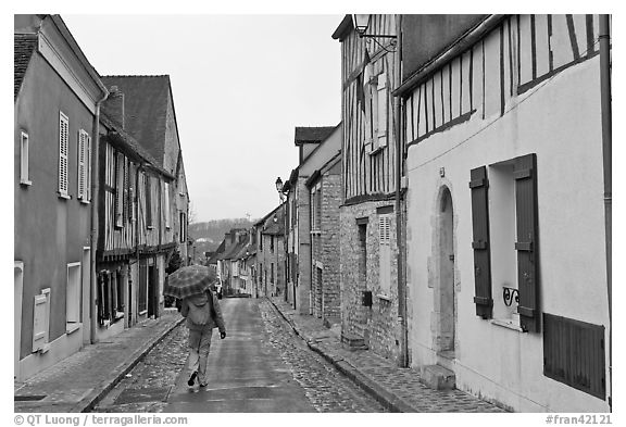 Pedestrian with umbrella in narrow street, Provins. France (black and white)