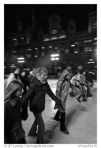 Girls skating by night, Hotel de Ville. Paris, France (black and white)