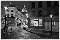 Cobblestone street, lamps, and Sacre-Coeur basilica by night, Montmartre. Paris, France (black and white)