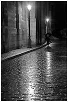Street lamps reflected in wet pavement, with woman walking. Paris, France ( black and white)