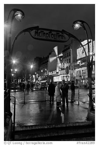 Art deco subway entrance and Moulin Rouge by night. Paris, France (black and white)