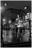 Art deco subway entrance and Moulin Rouge by night. Paris, France ( black and white)