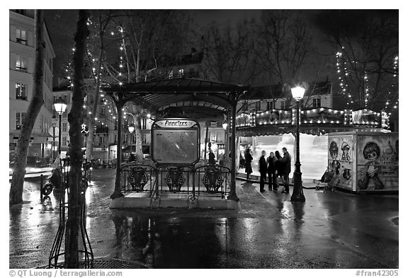 Square with subway entrance and carousel by night. Paris, France