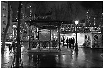 Square with subway entrance and carousel by night. Paris, France ( black and white)
