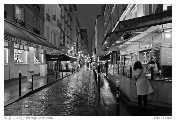 Woman buying food on street at night. Quartier Latin, Paris, France (black and white)