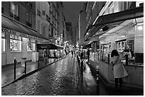 Woman buying food on street at night. Quartier Latin, Paris, France ( black and white)